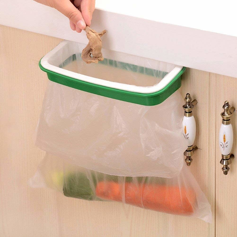 The holder clipped to a cabinet door, with a plastic bag inside and a hand putting food scraps inside it