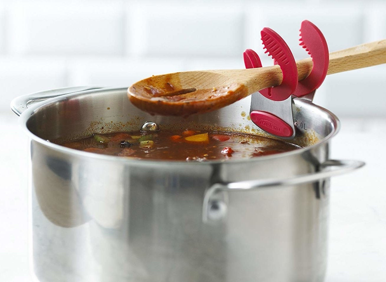The clips holding a wooden spoon over a pot of sauce or soup