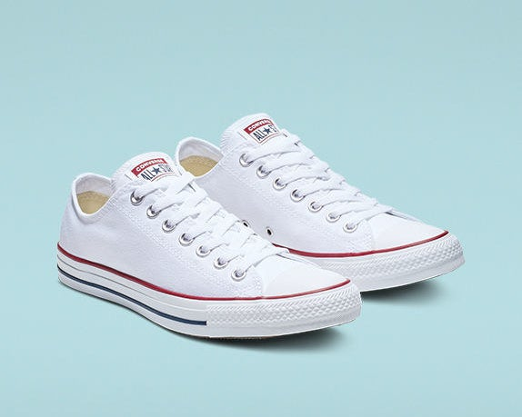 The shoes in white with a blue strip on the sole, a red strip right above the sole, and white laces