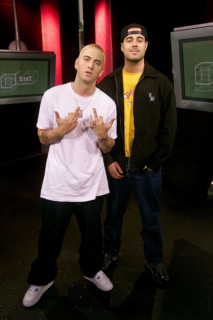 Eminem standing next to Carson Daly on the set of TRL in 2000