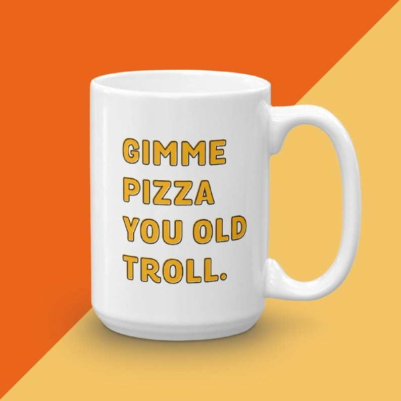 """a mug that says """"gimme pizza you old troll"""" on it"""