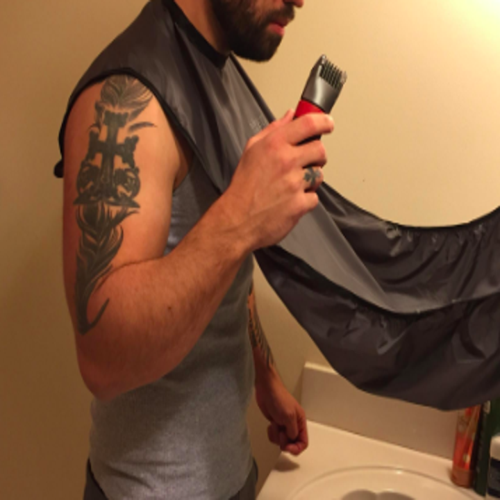 reviewer pic of person with a beard using the bib and holding a trimmer