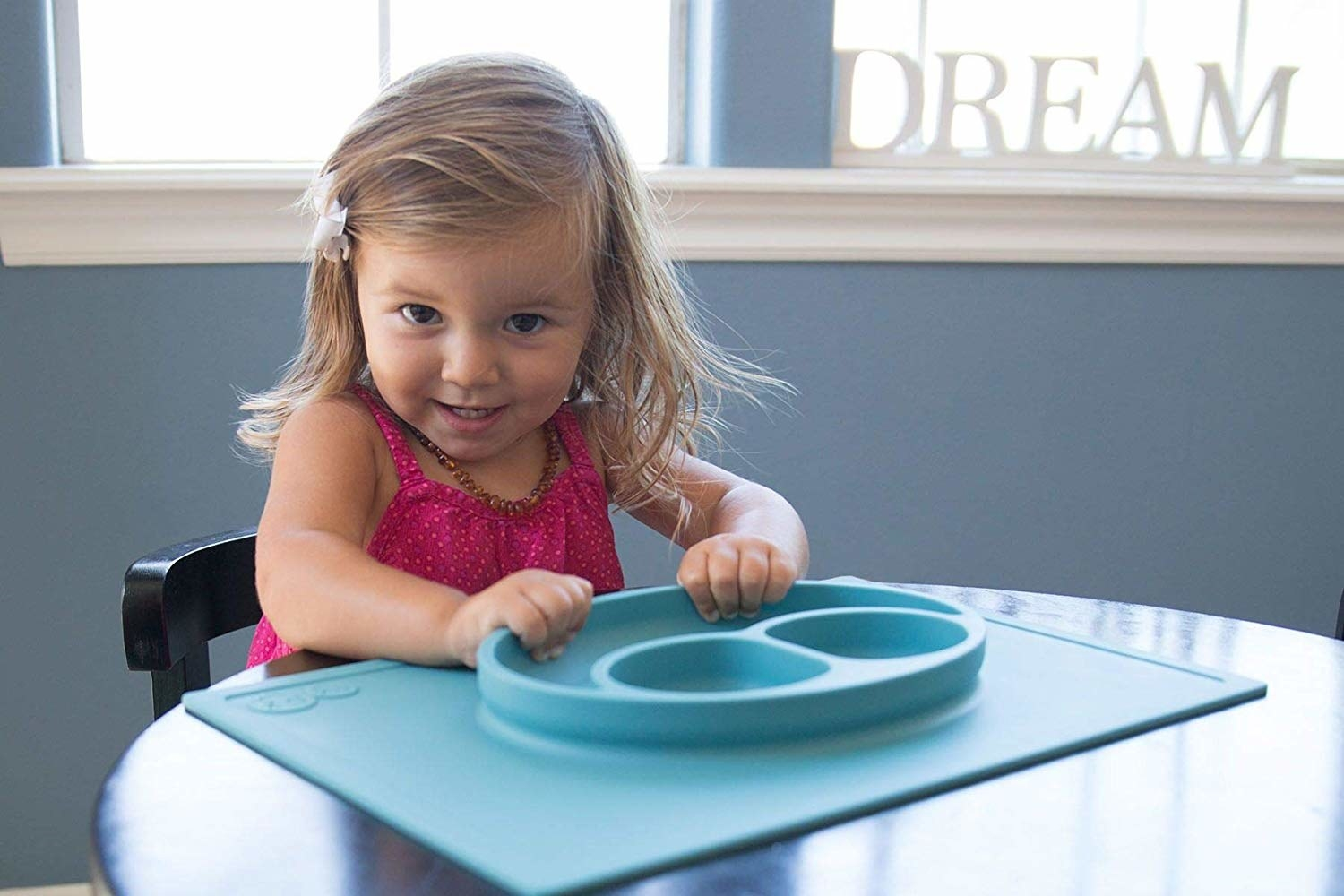 Toddler sitting at table with Happy Mat