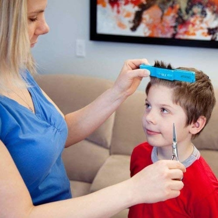 parent using the clip to cut a kid's bangs