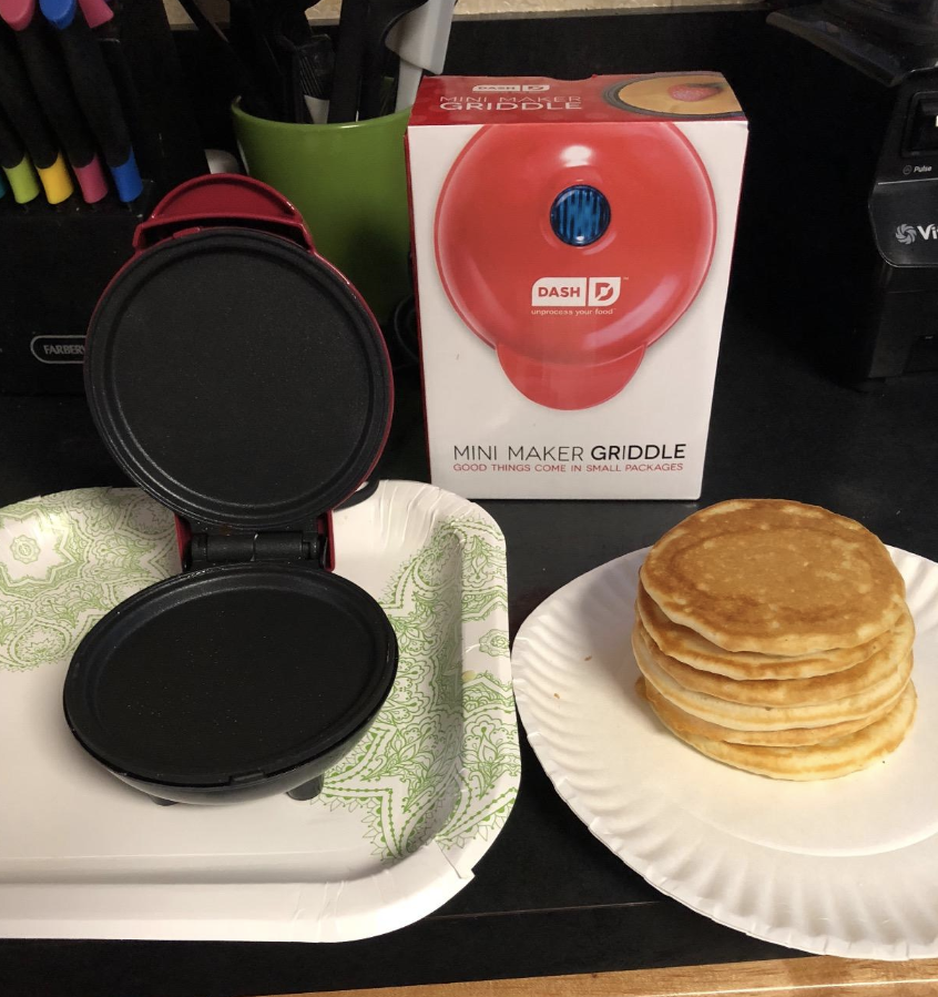 A reviewer photo of the Dash mini griddle open next to a stack of pancakes