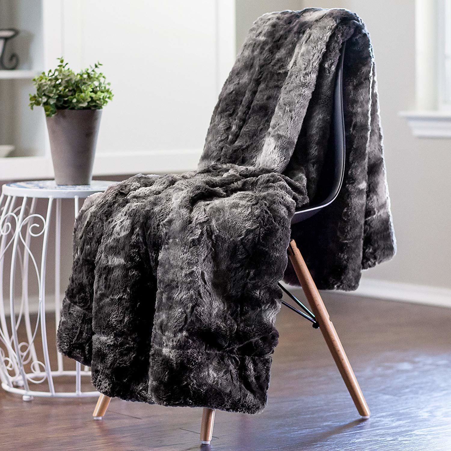 A super fuzzy throw in mottled greys draped across a chair