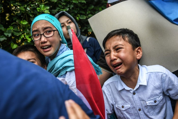 Children react as Turkish plainclothes police officers try to push back demonstrators during a protest of Uighur supporters outside the Chinese Consulate in Istanbul, July 2018.