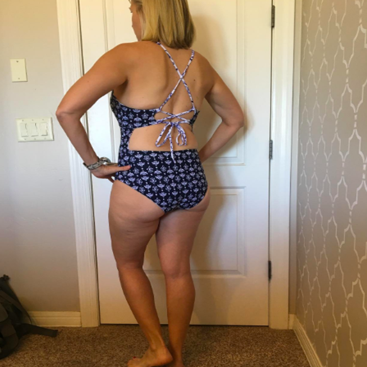the same reviewer wearing the suit reversed to a navy and white print, showing off the strappy back