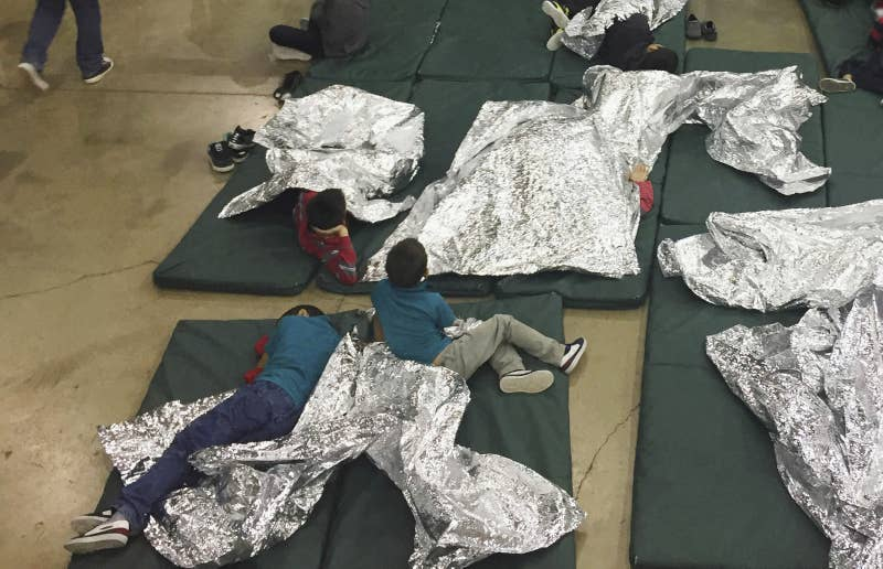 In this June 17, 2018, file photo, people, including children, who have been taken into custody related to cases of unauthorized entry into the United States rest in cages at a facility in McAllen, Texas.