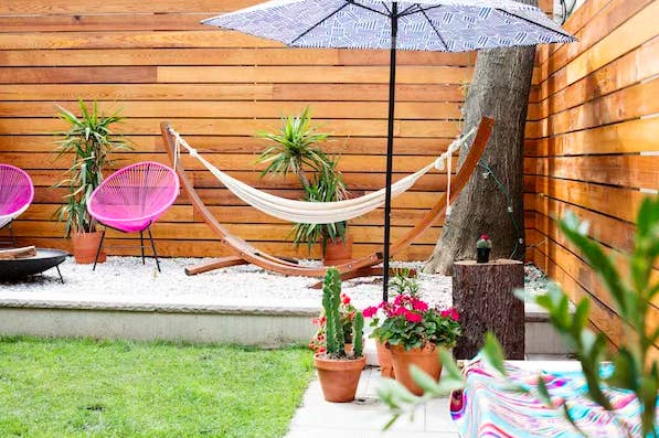 backyard with hammock and umbrella and container plants in it