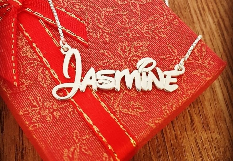 "a gold necklace that says ""jasmine"" in Disney script"