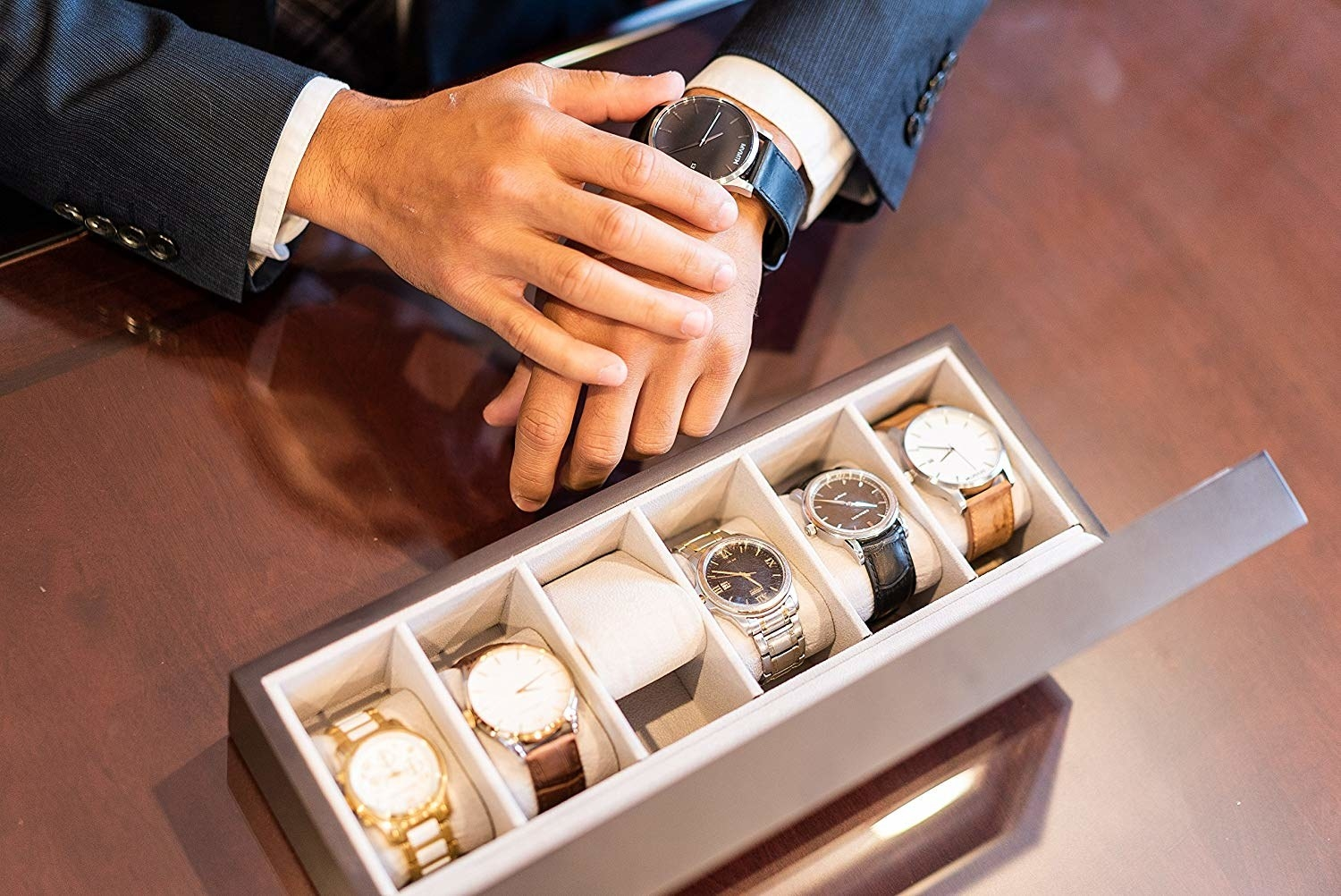A wood and glass display box with room for six wrist watches