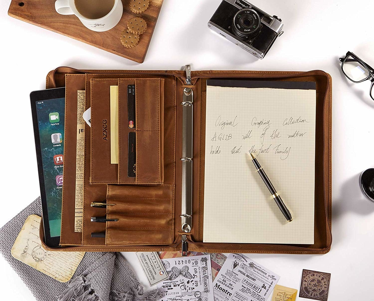 An open three ring portfolio with pockets for cards, an Ipad, and pens