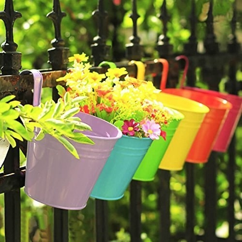 a row of colorful buckets with plants in them