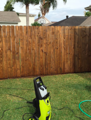 the same fence looking vibrant brown wafter using the pressure washer