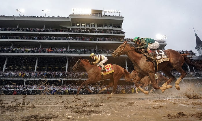 Flavien Prat rides Country House, left, to the finish line during the 145th running of the Kentucky Derby horse race at Churchill Downs, May 4, in Louisville, Kentucky.