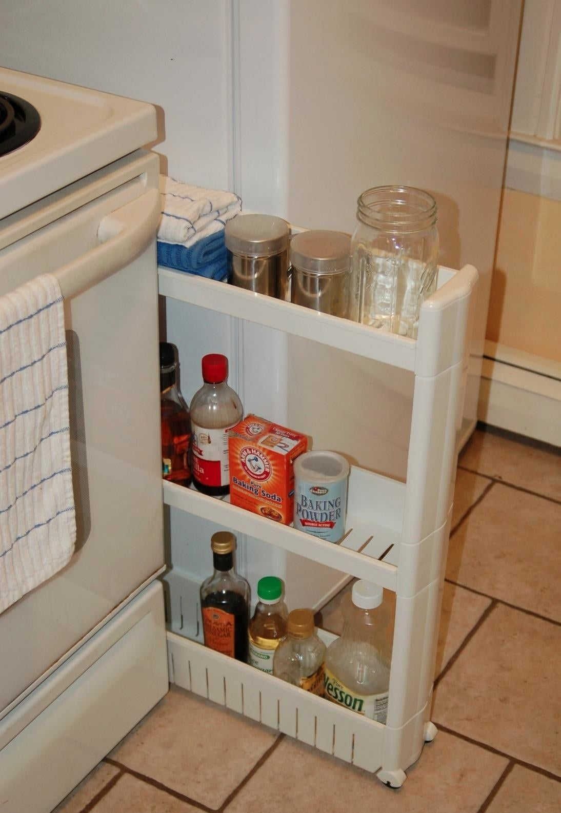 Reviewer photo of the storage tower with three shelves filled with food and cooking ingredients between a stove and fridge