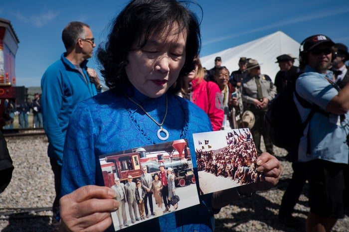 Connie Young Yu, descendant of 19th-century railroad workers, shows photographs of her parents from the centennial anniversary of the Transcontinental Railroad before making the opening remarks at the 150th anniversary. Her parents were denied the opportunity to speak during the 100th anniversary in 1969.