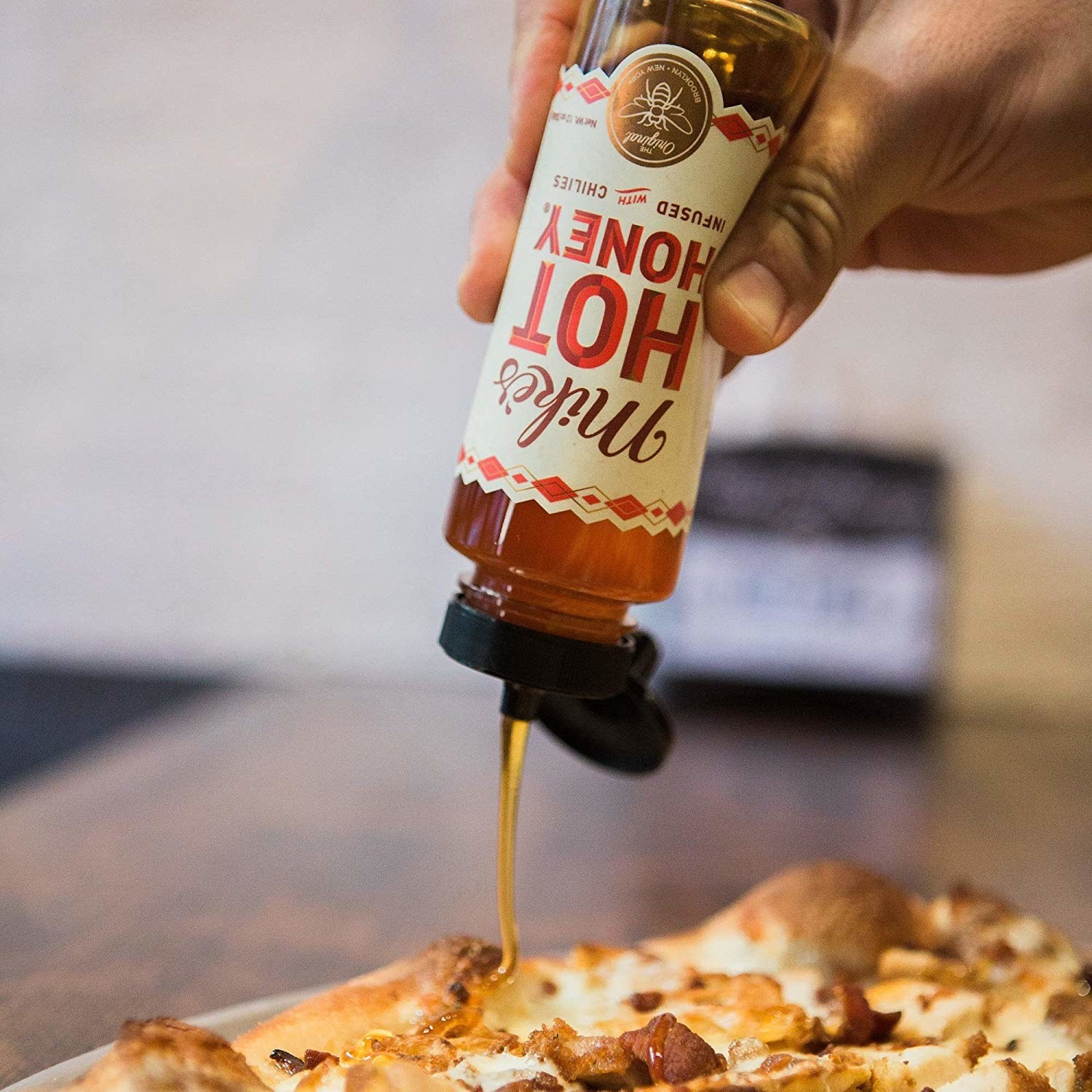 An image of the honey being drizzled onto pizza