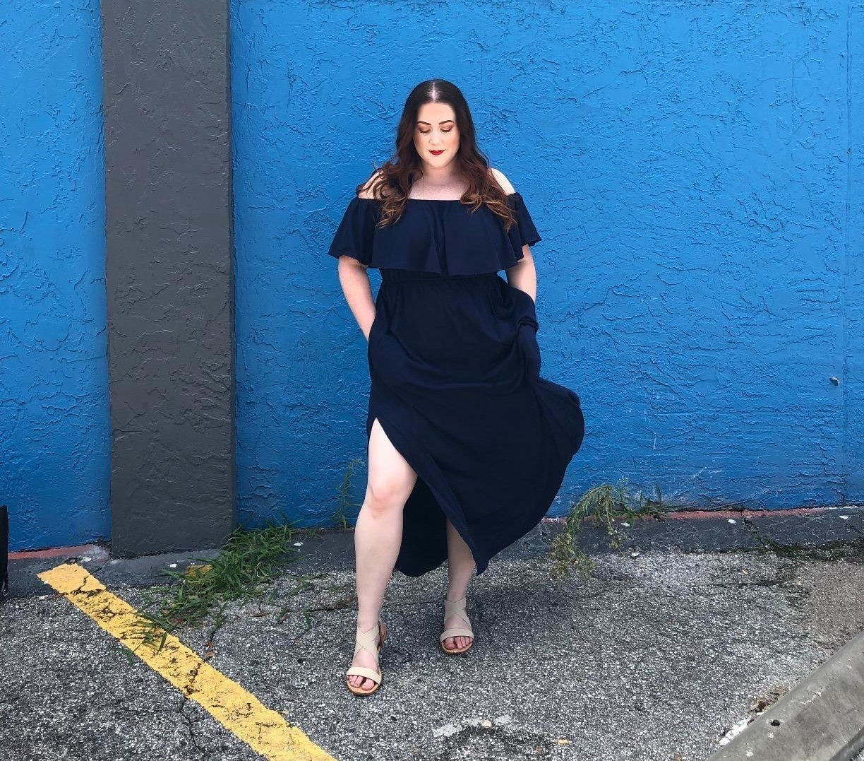 A reviewer modeling the maxi dress and showing off the thigh-high side slit