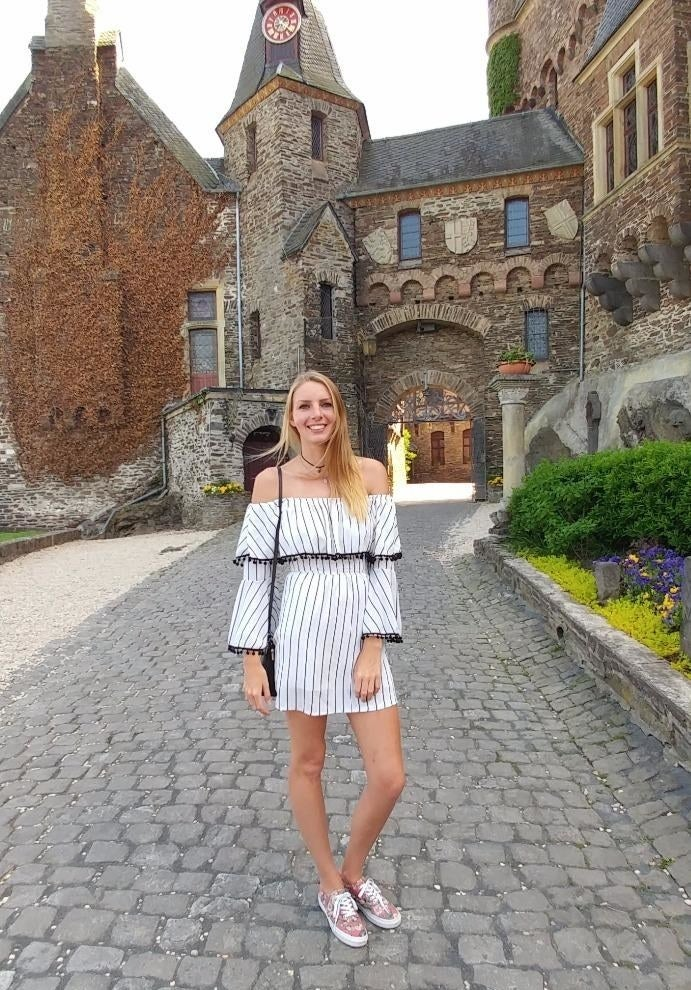 A reviewer wearing the mini dress, which has an off-the-shoulder design, in the long-sleeve version