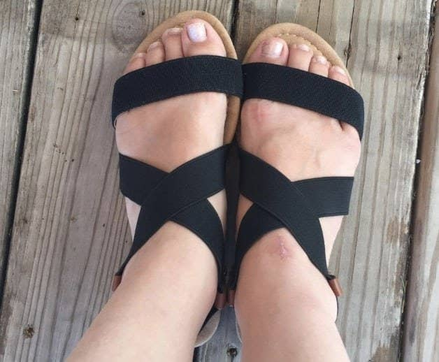 a reviewer's feet in the black strappy sandals
