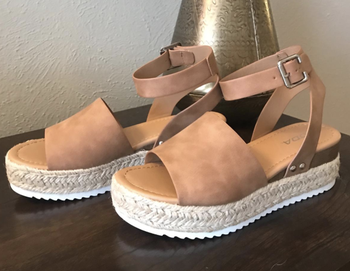a reviewer's photo of the shoes with a ankle strap and buckle in tan