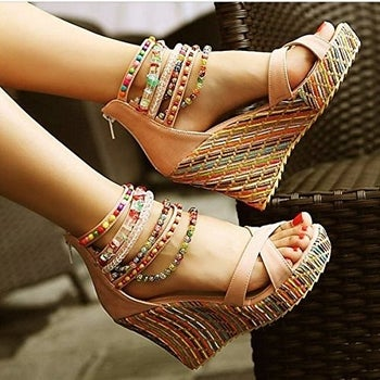 a model wearing the beaded wedge sandals in a light tan color with a zip-up back and beading around the ankles