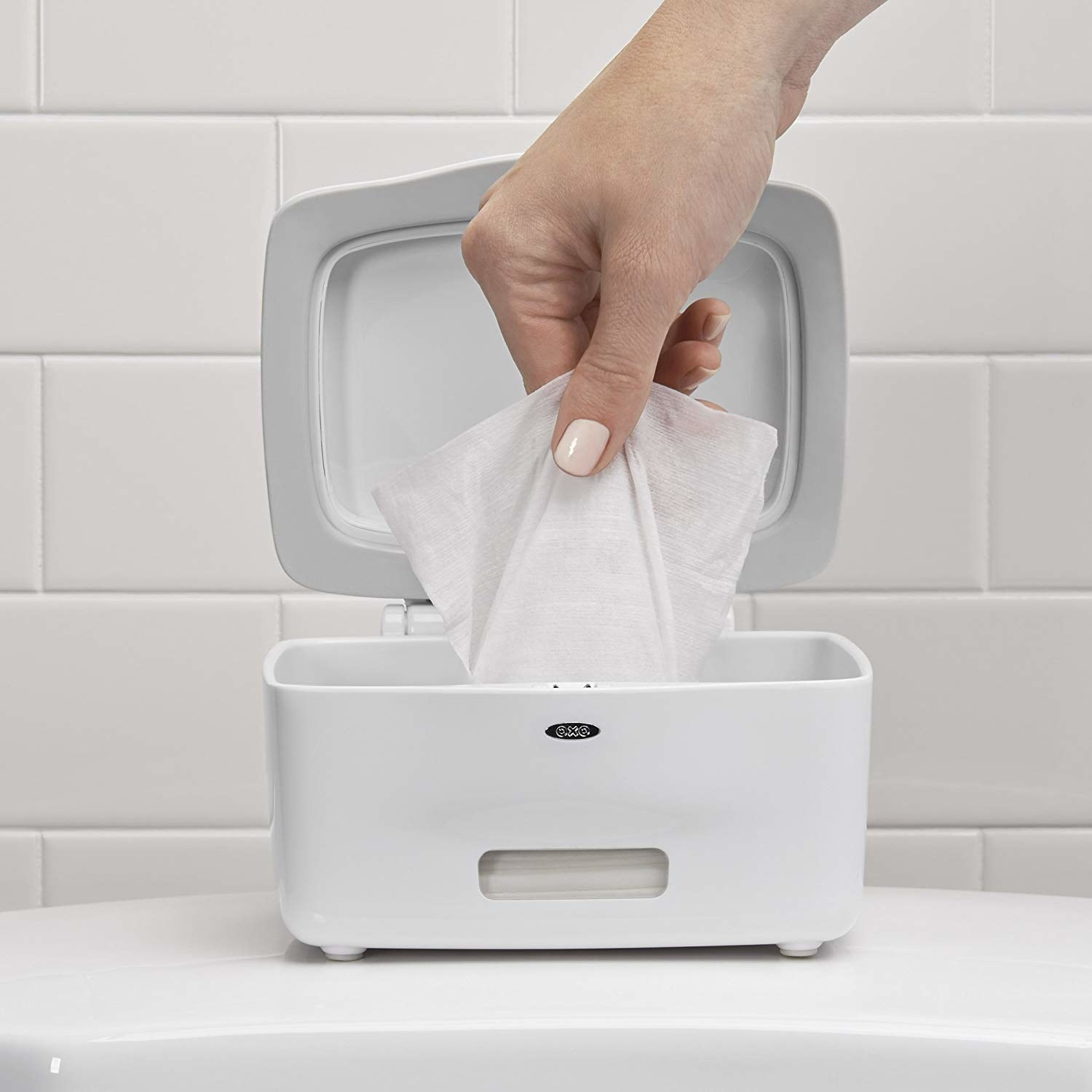 a hand reaching in to pull out a wipe from the dispenser