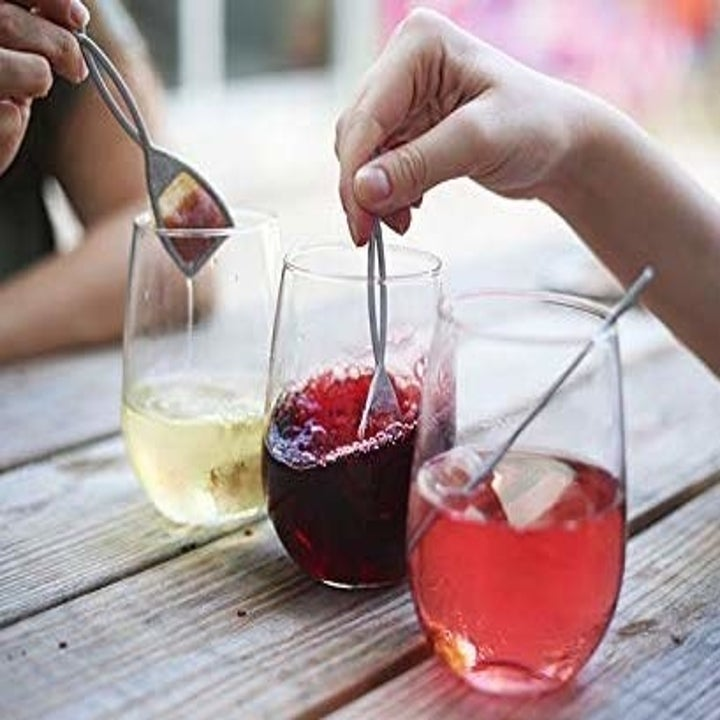 person swirling wine wand in their wine