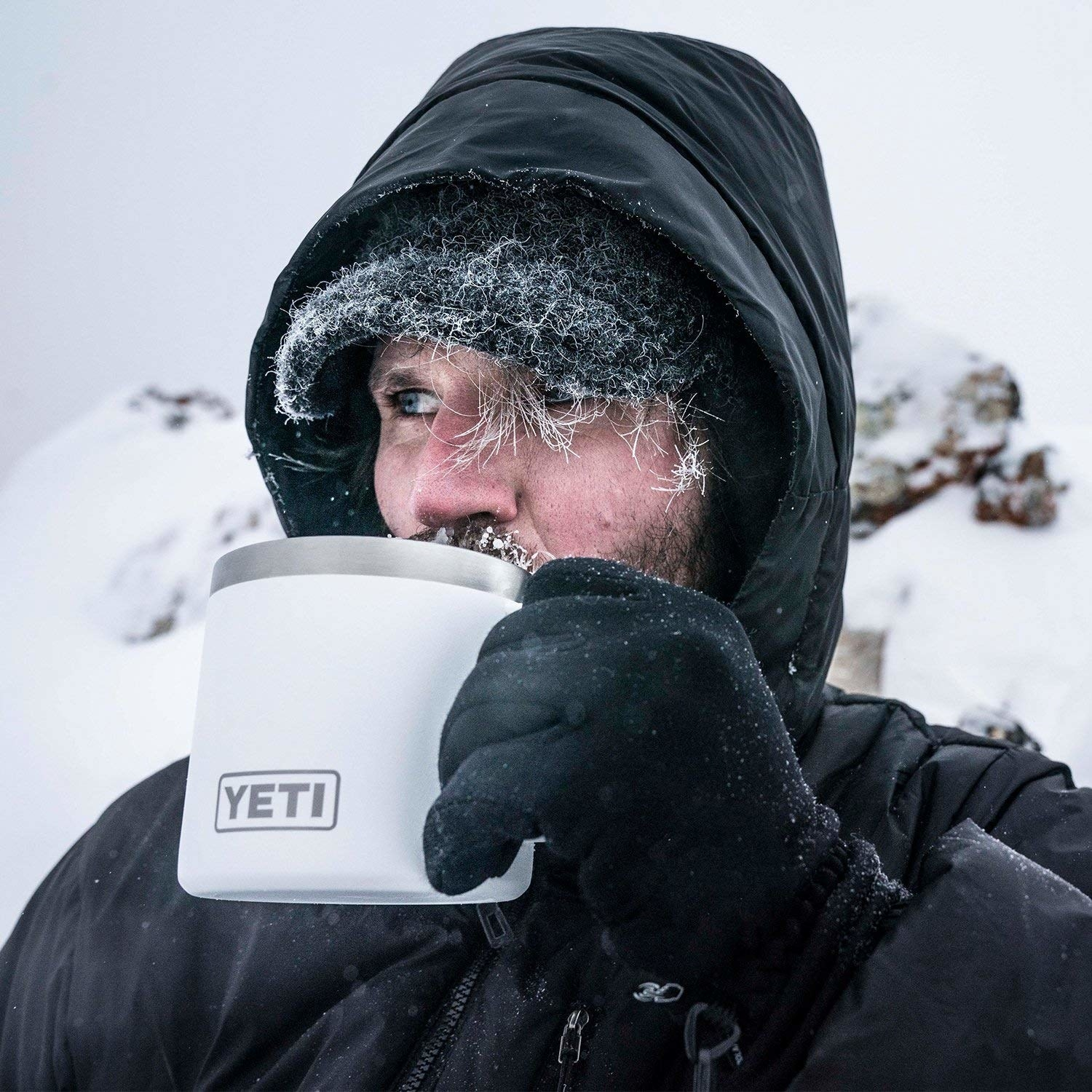 A man in the snowy outdoors is in a parka dusted with snow and drinking from a white Yeti mug.