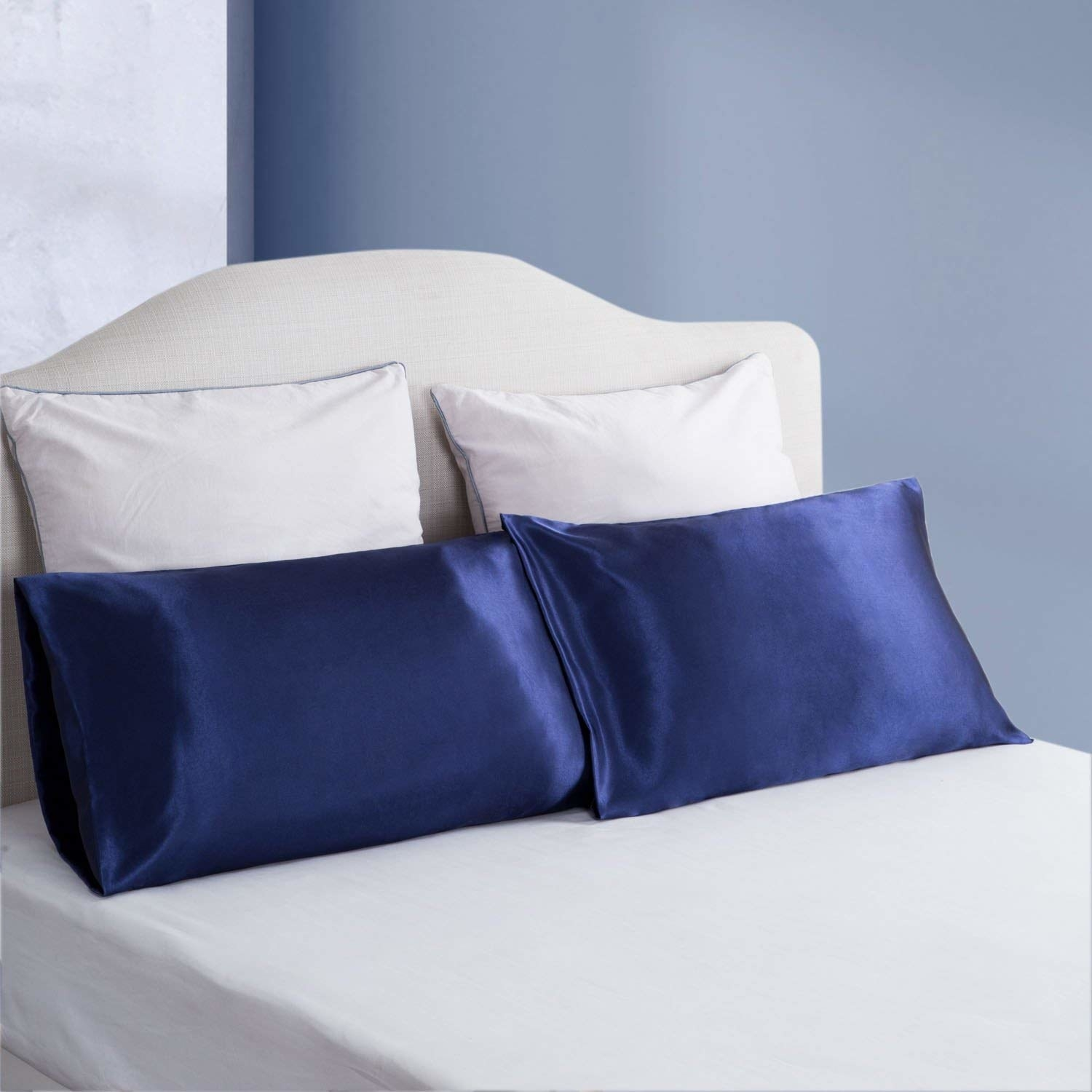 navy blue satin pillowcases on pillow on made up bed