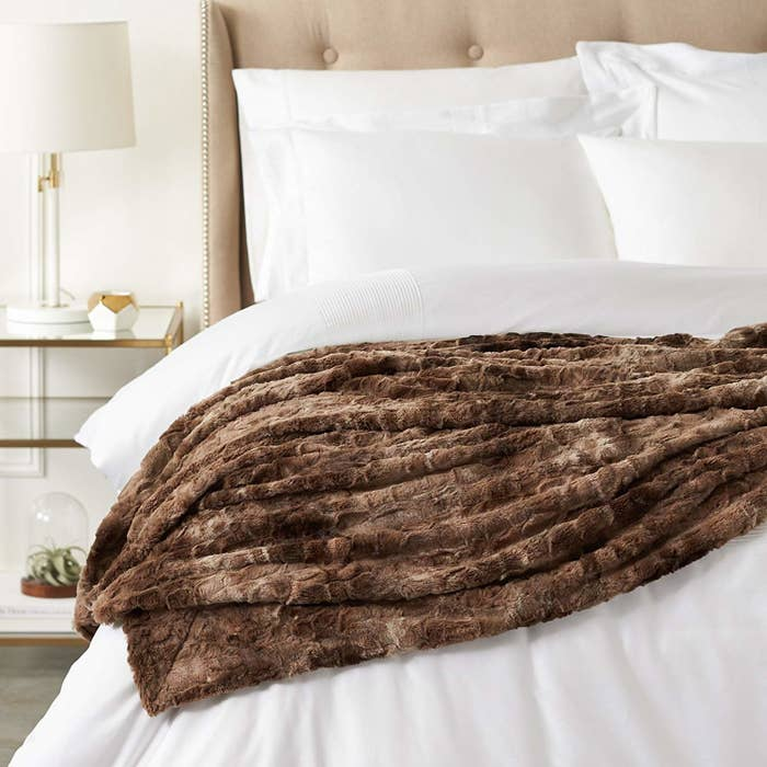 bed with faux fur throw across the comforter
