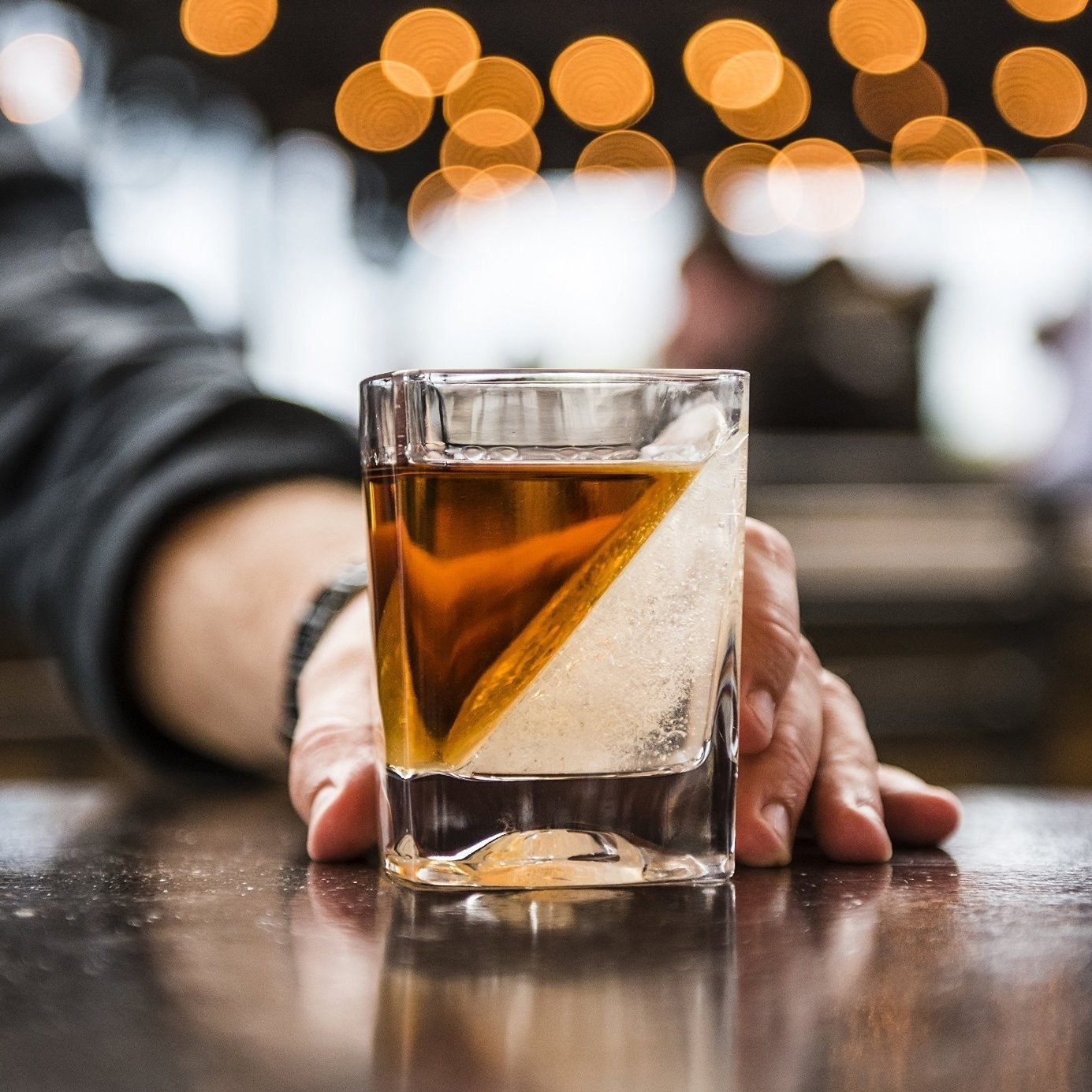 A hand holding the whiskey glass