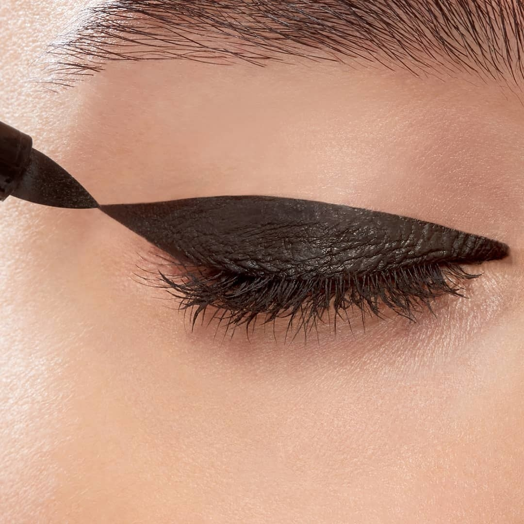 Model applying a bold cat-eye with the thick-tipped eyeliner