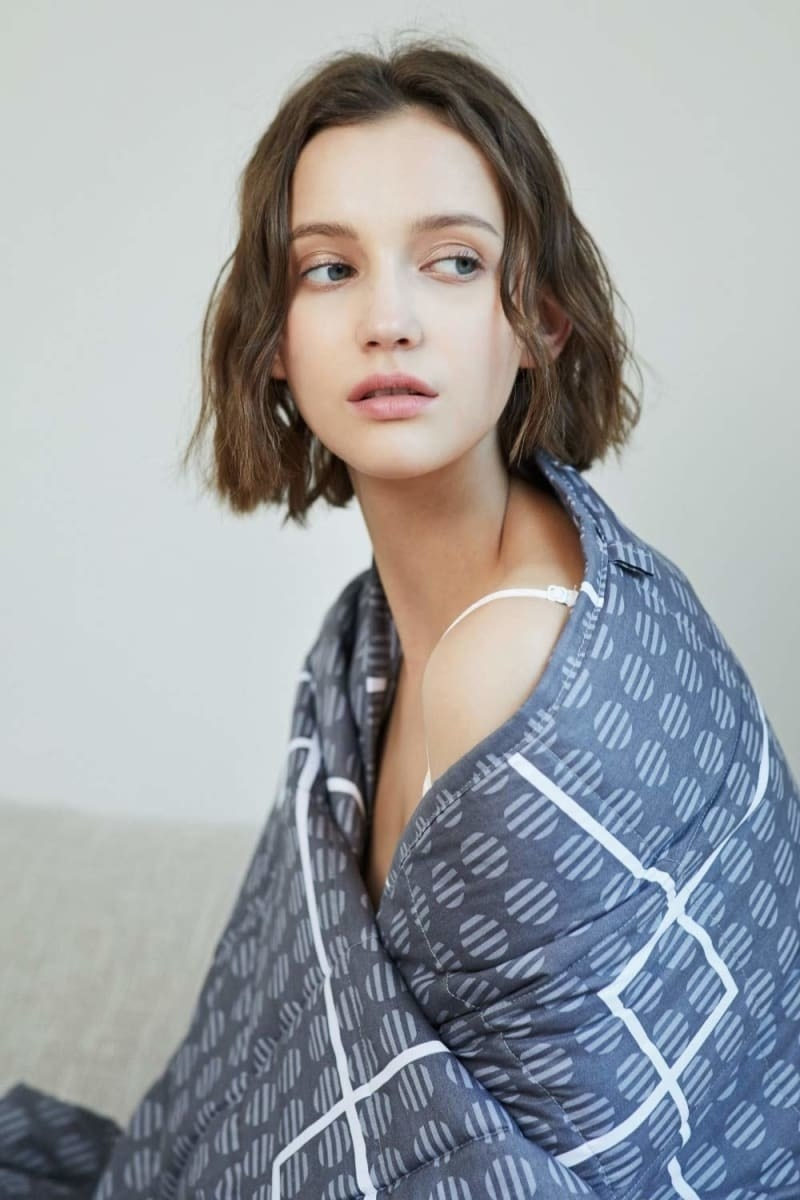 a model with the weighted blanket wrapped around their shoulders