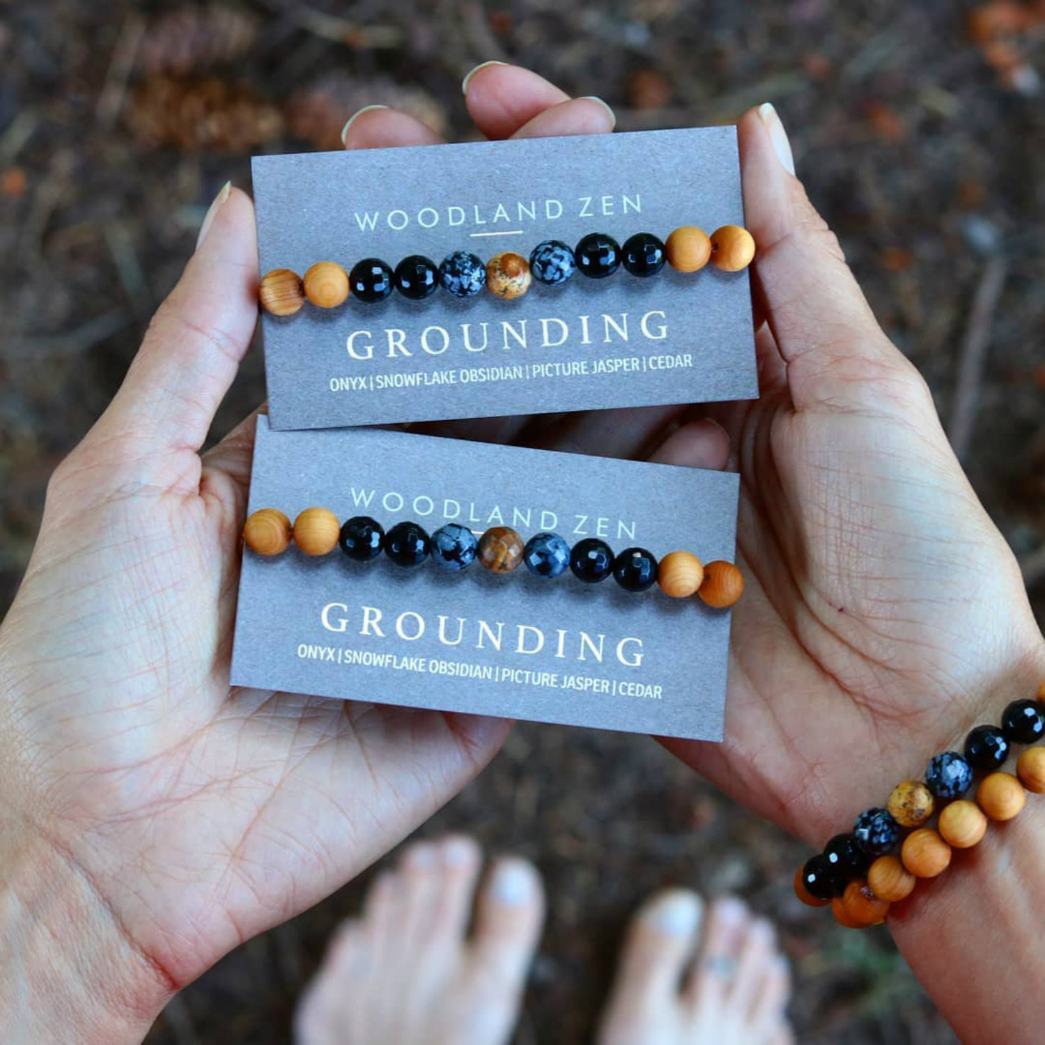 a person holding two of the grounded bracelets in their hand while also wearing the stones