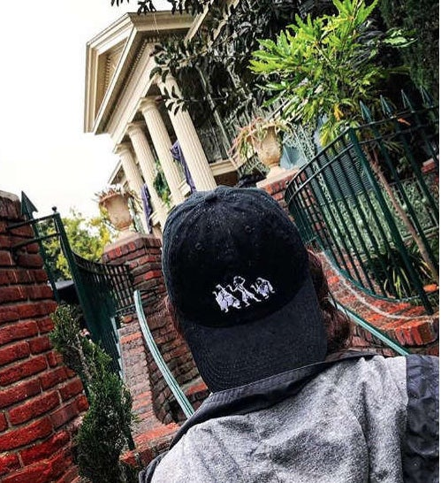 black baseball cap with the ghosts from haunted mansion embroidered on it