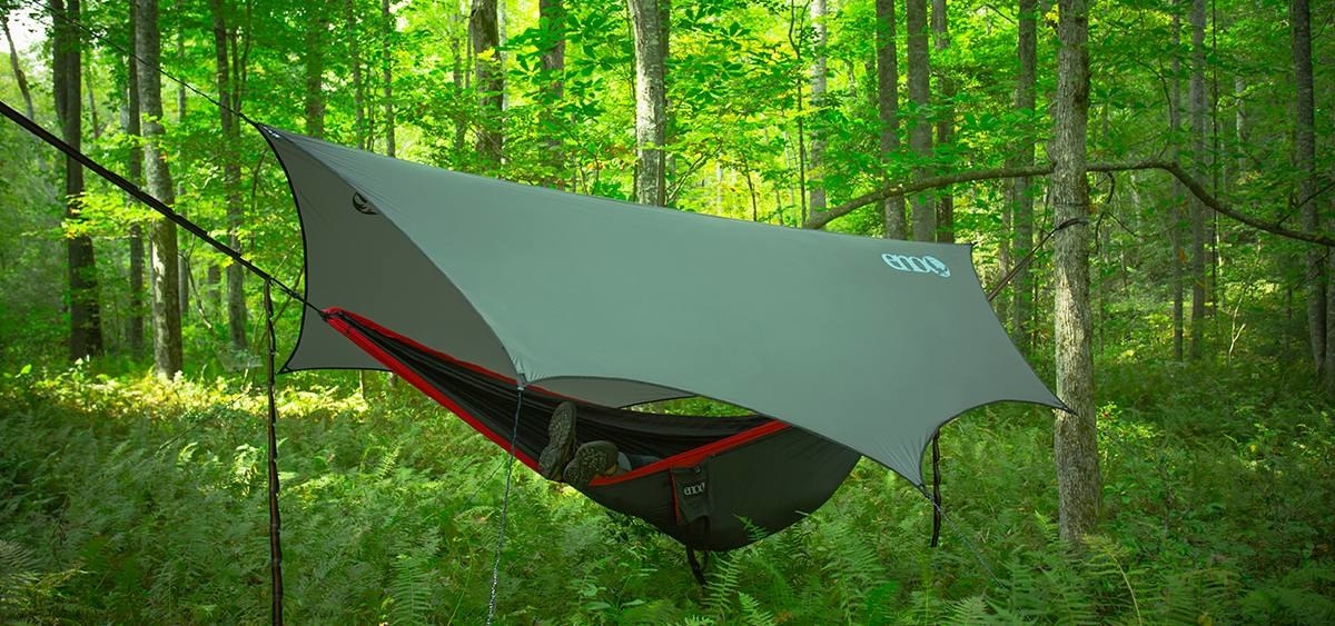 A hanging hammock in the woods covered by a thin, triangular tarp