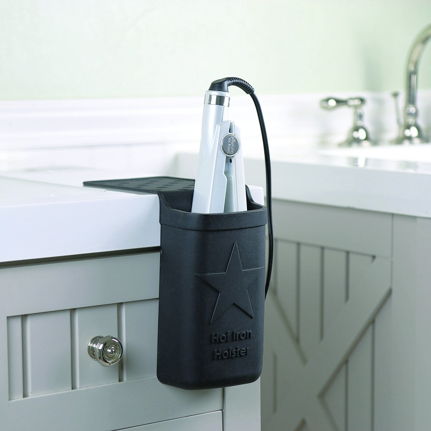 the holster holding a hair straightener on the edge of a bathroom vanity