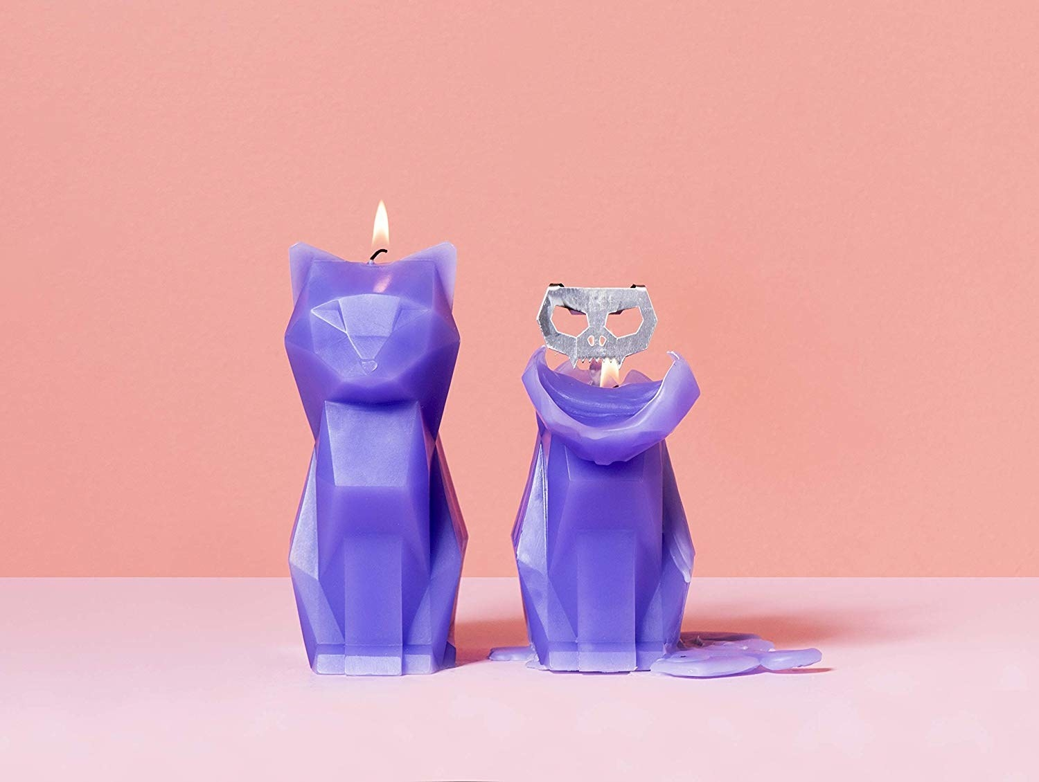 geometric cat candle next to a half melted candle with metal cat skeleton inside