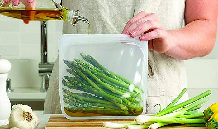 Person drizzling in oil into a Stasher bag with asparagus in it
