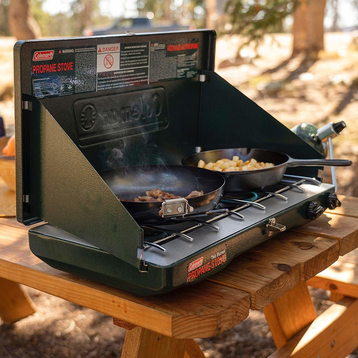 The fold-open stove, set on a picnic table, cooking bacon in one skillet and potatoes and the other