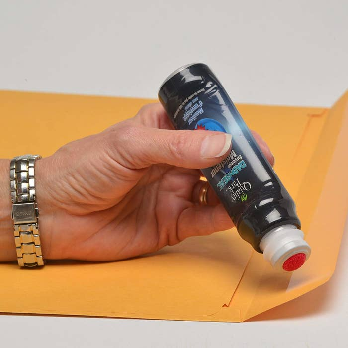 A person holding the envelope sealer