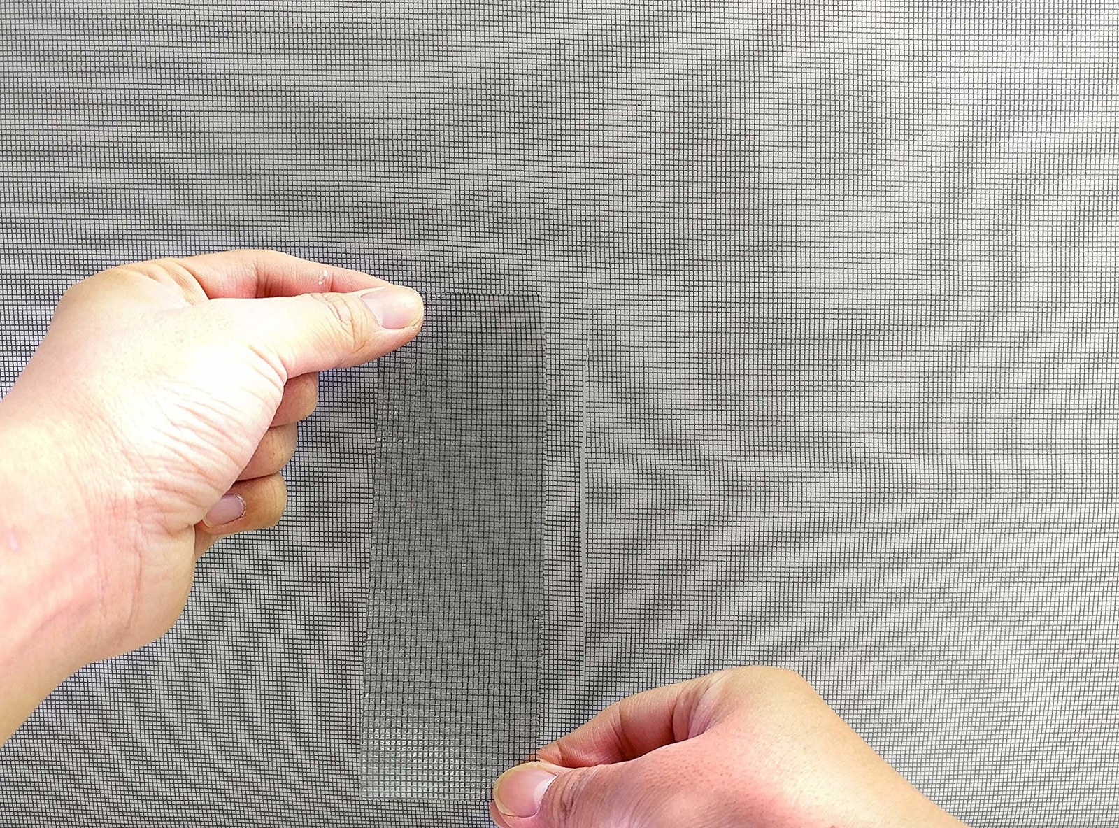 hands placing the screen tape on a screen
