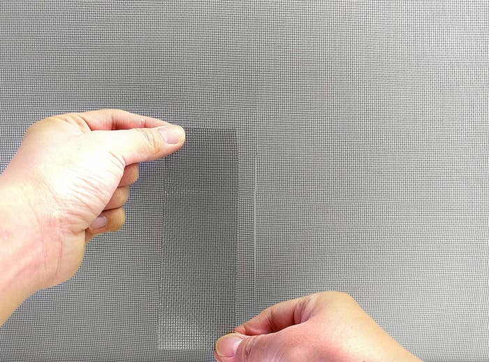 Hand placing the screen repair tape on a matching screen