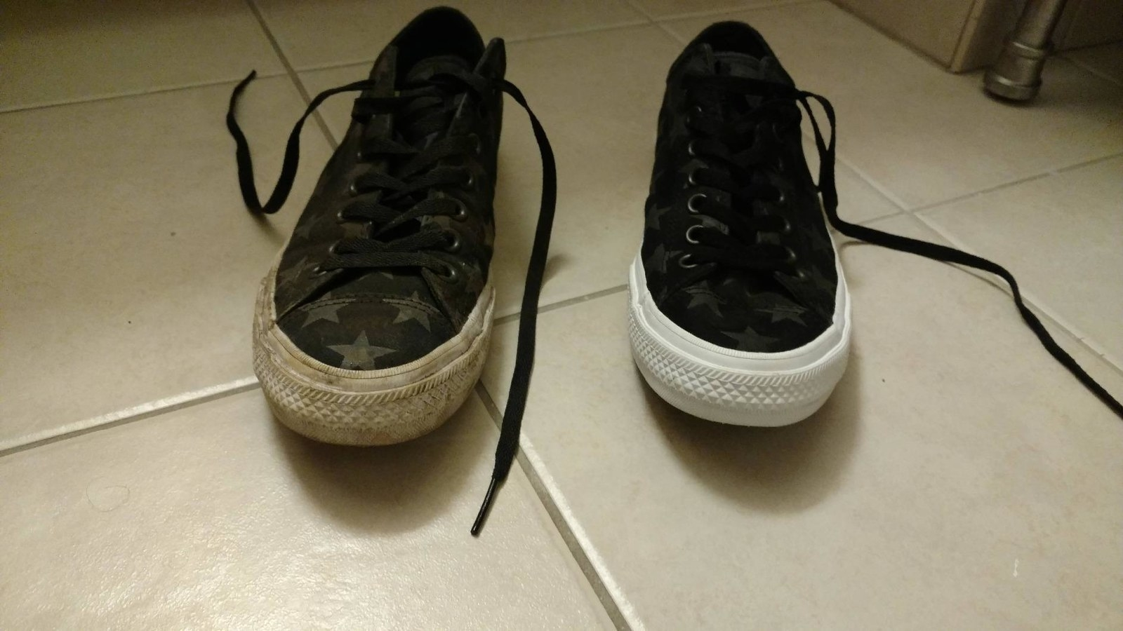 A reviewer's sneakers: one very dirty with the thick white soles tinted brown, the other completely clean and brand new looking
