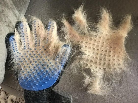 Reviewer's picture of the pet hair removal glove covered in fur, with another fur pile next to it