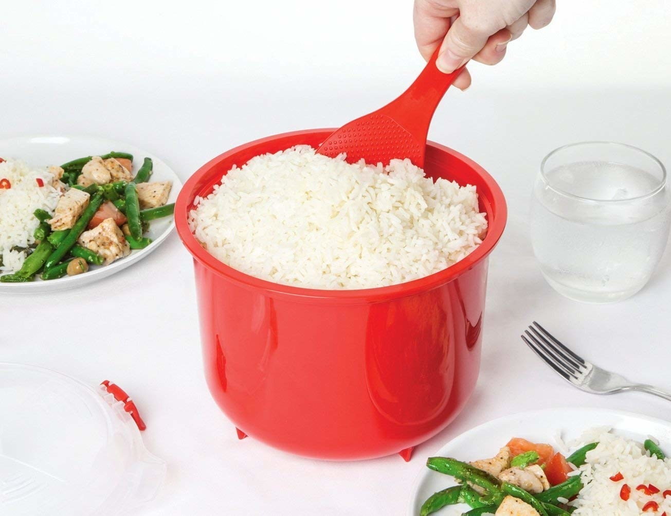 A hand scooping rice from the red plastic steamer with a paddle