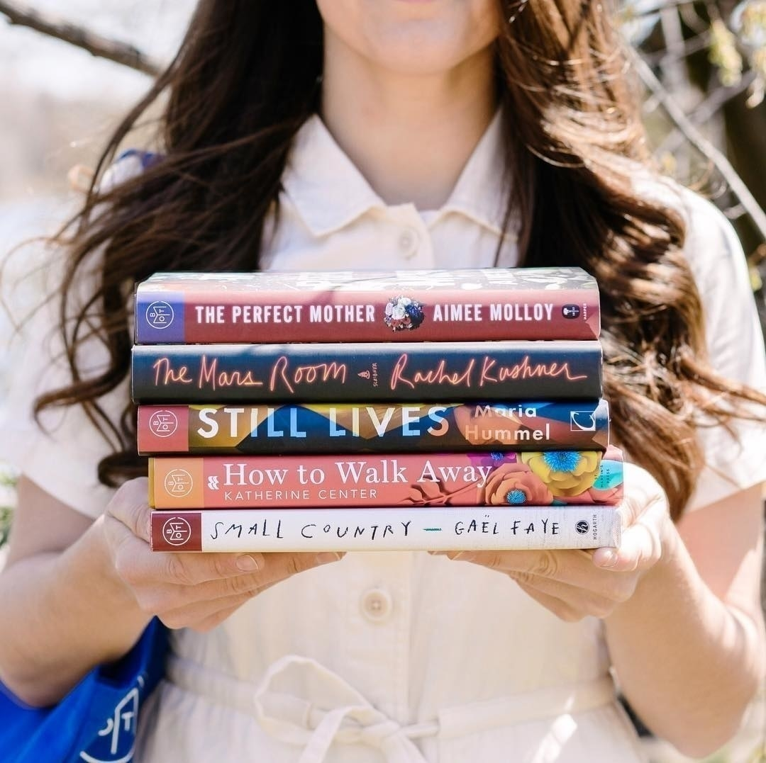 Model holding five books (each an option for a specific month): The Perfect Mother, The Mars Room, Still Lives, How To Walk Away, and Small Country
